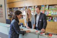 Duales Studium Stadt Münster – Zwei Personen informieren eine junge Frau mit Informationsflyern über Ausbildungsmöglichkeiten